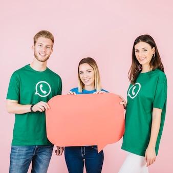 Porträt von drei glücklichen freunden, die leere grüne spracheblase halten