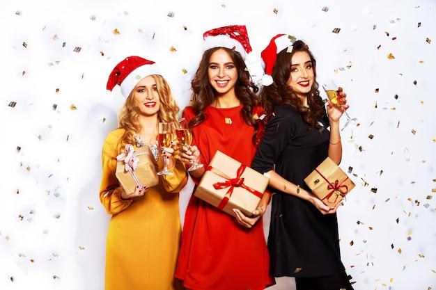 Porträt von drei glücklichen jungen frauen im weihnachtsmannhut mit geschenk und wunderkerzen.