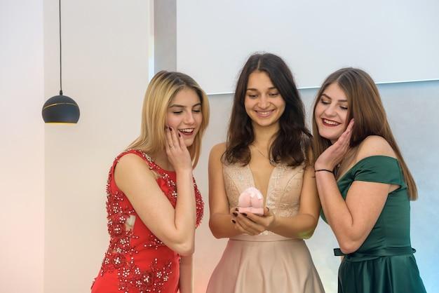 Porträt von drei glücklichen jungen frauen, weihnachtskonzept mit geschenkbox und in abendkleidern auf party