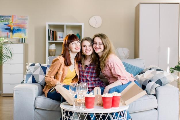 Porträt von drei glücklichen jungen freundinnen, die hausparty mit pizza, popcorn und wein haben, die auf dem grauen sofa im esszimmer zu hause sitzen. pizza party, weibliche freundschaft