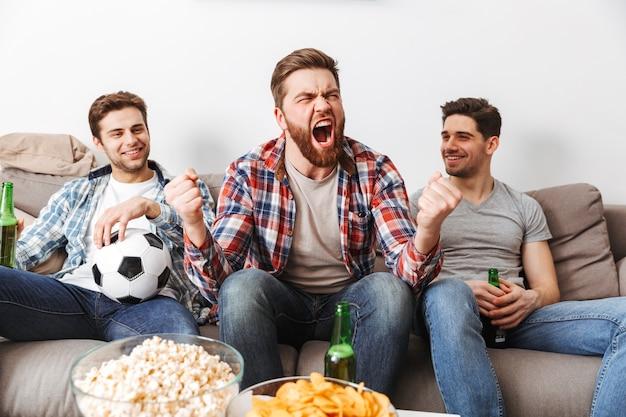 Porträt von drei glücklichen jungen männern, die fußball schauen, während sie zu hause mit bier und snacks drinnen sitzen