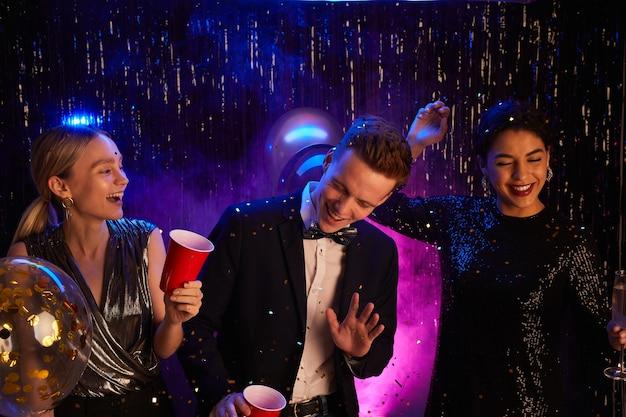 Porträt von drei glücklichen teenagern, die tanzen und lachen, während sie abschlussballnacht genießen