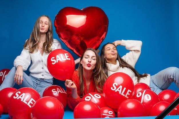 Porträt von drei hübschen lächelnden freundinnen in freizeitkleidung, die mit roten luftballons mit verkauf und prozentzeichen sitzen