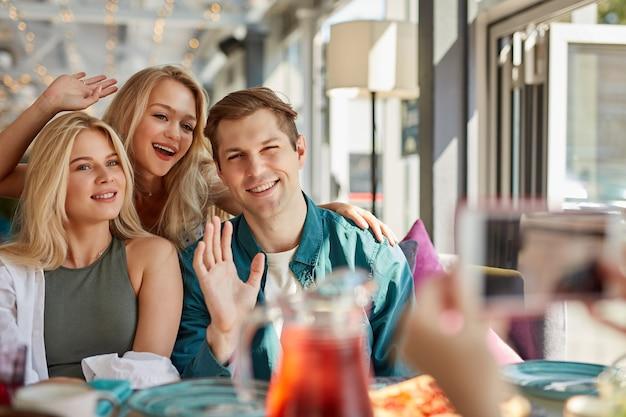 Porträt von drei jungen besten freunden, die im café sitzen