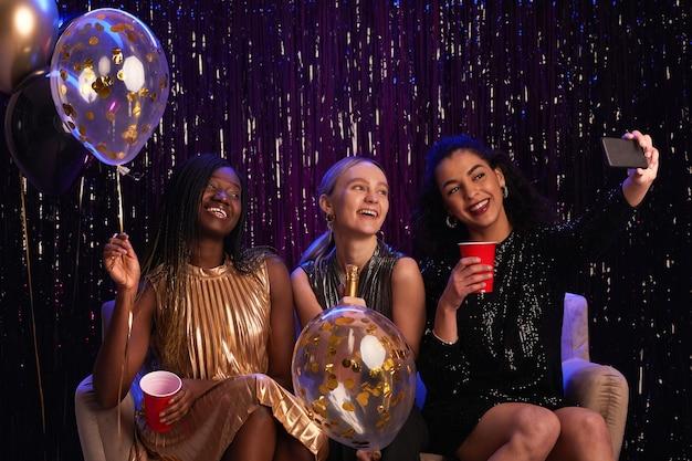 Porträt von drei jungen frauen, die auf der party ein selfie-foto machen, während sie funkelnde kleider tragen