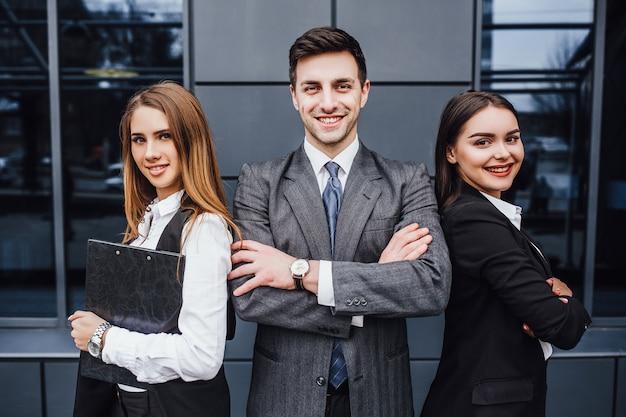 Porträt von drei jungen lächelnden rechtsanwälten, die gekreuzte arme stehen.