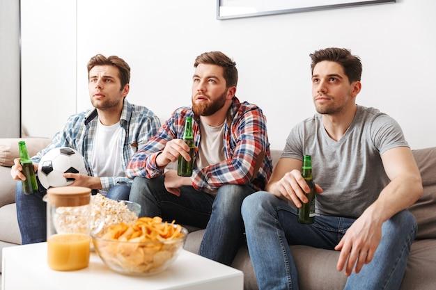 Porträt von drei jungen männern, die fußball schauen, während sie zu hause sitzen, bier trinken und snacks essen