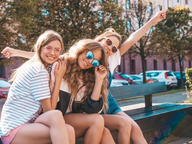 Porträt von drei jungen schönen lächelnden hippie-mädchen in der modischen sommerkleidung sexy sorglose frauen, die auf der bank in der straße sitzen positive modelle, die spaß in der sonnenbrille haben hände anheben