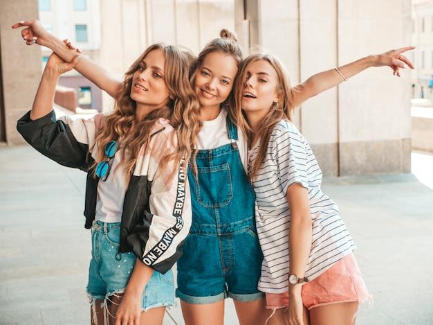 Porträt von drei jungen schönen lächelnden hippie-mädchen in der modischen sommerkleidung. sexy sorglose frauen, die auf der straße aufwerfen positive modelle, die spaß haben umarmen