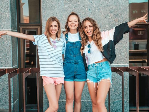 Porträt von drei jungen schönen lächelnden hippie-mädchen in der modischen sommerkleidung. sexy sorglose frauen, die auf der straße aufwerfen positive modelle, die spaß haben und hände anheben