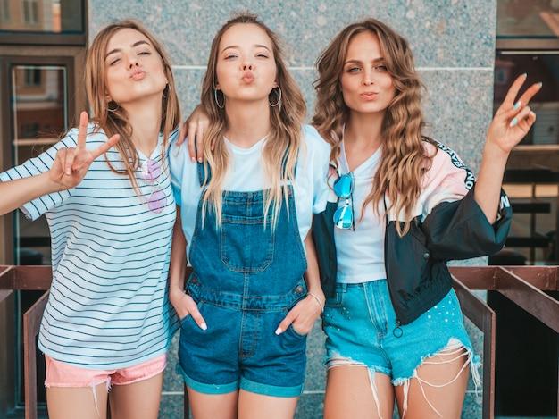 Porträt von drei jungen schönen lächelnden hippie-mädchen in der modischen sommerkleidung. sexy sorglose frauen, die auf der straße aufwerfen positive modelle, die spaß haben. zeigt friedenszeichen