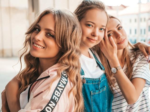 Porträt von drei jungen schönen lächelnden hippie-mädchen in der modischen sommerkleidung. sexy sorglose frauen, die auf der straße aufwerfen. positive modelle, die spaß haben