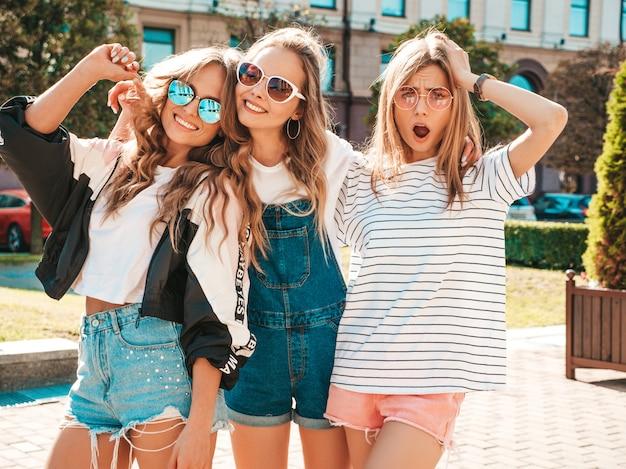 Porträt von drei jungen schönen lächelnden hippie-mädchen in der modischen sommerkleidung. sexy sorglose frauen, die auf der straße aufwerfen positive modelle, die spaß in der sonnenbrille haben umarmen