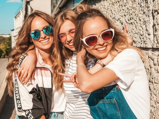 Porträt von drei jungen schönen lächelnden hippie-mädchen in der modischen sommerkleidung. sexy sorglose frauen, die in der straße nahe wand aufwerfen positive modelle, die spaß in der sonnenbrille haben umarmen