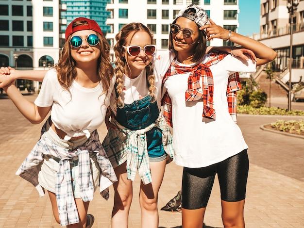 Porträt von drei jungen schönen lächelnden hipster-mädchen in der trendigen sommerkleidung