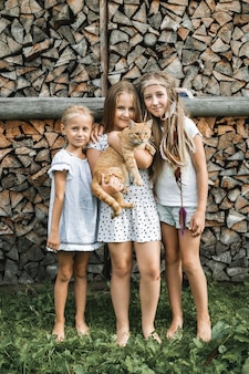 Porträt von drei kleinen hübschen mädchen, schwestern, in freizeitkleidung, die zusammen auf dem hintergrund des gestapelten brennholzes stehen