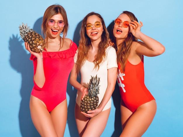 Porträt von drei lächelnden brunettemodellen der mode in der sommerbadebekleidungskleidung. mädchen mit frischen ananas. frau in der runden sonnenbrille, die spaß und die aufstellung hat