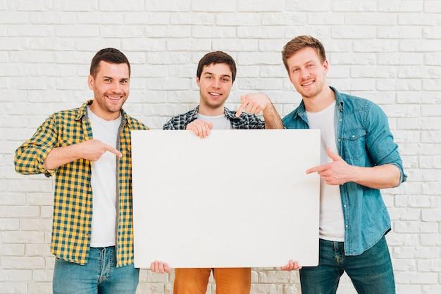 Porträt von drei männlichen freunden, die weißes leeres plakat zeigen