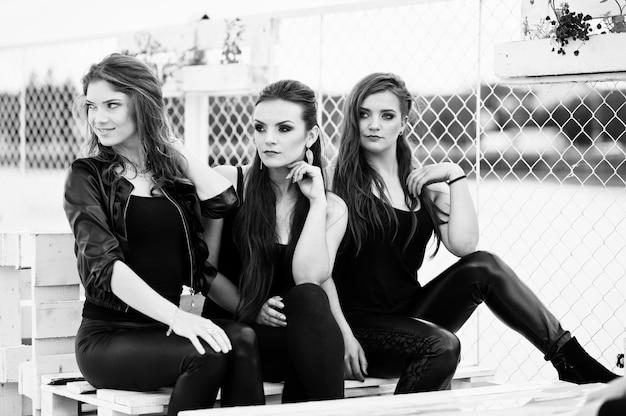 Porträt von drei modemädchen, die auf bank am pier sitzen