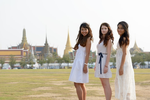 Porträt von drei multiethnischen jungen schönen frauen als freunde zusammen im park draußen