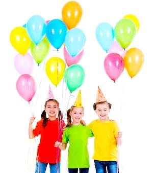 Porträt von drei niedlichen kleinen mädchen mit farbigen luftballons - lokalisiert auf einem weiß
