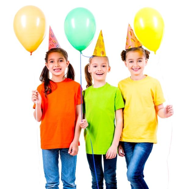 Porträt von drei niedlichen kleinen mädchen mit farbigen luftballons und partyhut - lokalisiert auf einem weiß