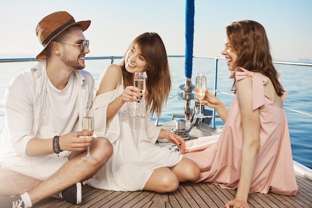 Porträt von drei personen, die auf dem boden der yacht sitzen, während sie champagner trinken und lachen und luxuriösen urlaub genießen. zwei beste freunde verliebten sich in denselben kerl und flirten jetzt mit ihm.