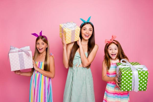 Porträt von drei personen halten erhalten geschenkbox für 8-märz mit blonden brünetten haarschnitt tragen hellen stirnband rock über rosa isoliert