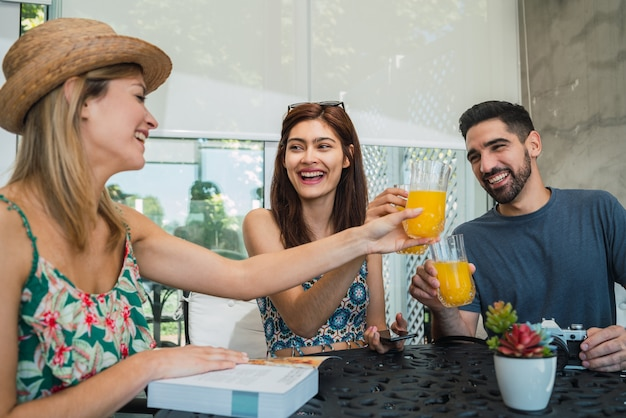 Porträt von drei reisenden freunden, die einige zeit verbringen und ihre reise im hotel organisieren. reise- und lifestyle-konzept.