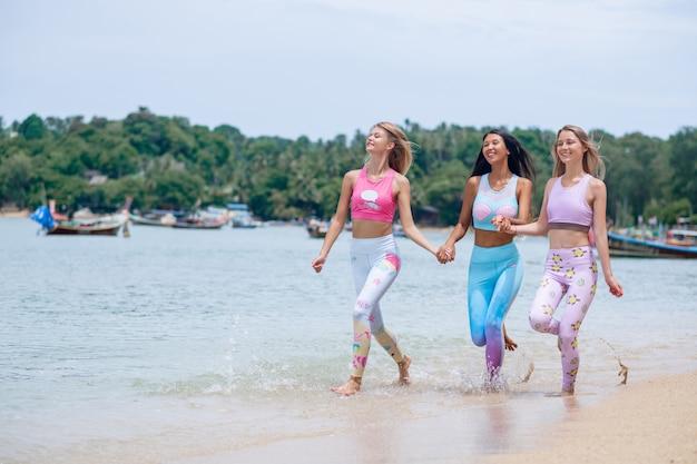 Porträt von drei schlanken mädchen in den bunten fitnessanzügen, die kamera am strand beim gehen auf dem sandstrand lächeln.