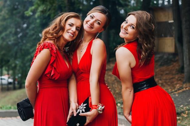 Porträt von drei schönen brautjungfern im roten kleid