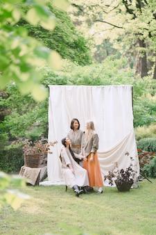 Porträt von drei schönen frauen im garten, stehend, sitzend und lächelnd während des tages.