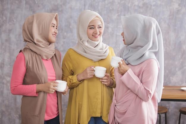 Porträt von drei schönen muslimischen frau stehend, während sie eine kaffeezeit zusammen haben