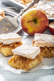 Porträt von drei stücken eines apfelkuchens mit einem verquirlten wgg-weiß, das auf einer serviette mit mehr kuchen und frischen äpfeln auf der rückseite liegt.