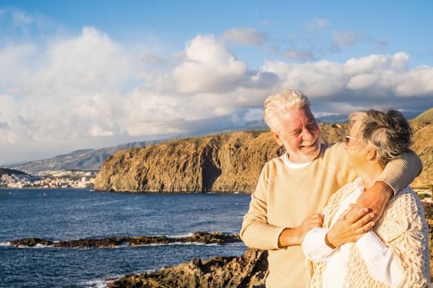Porträt von ein paar reifen und alten leuten, die den sommer am strand genießen und auf das meer schauen, lächeln und spaß haben zusammen mit dem sonnenuntergang im hintergrund. zwei aktive senioren, die im freien reisen.