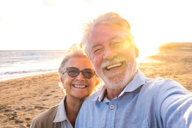 Porträt von ein paar reifen und alten menschen, die den sommer am strand genießen und auf die kamera schauen, die zusammen mit dem sonnenuntergang im hintergrund ein selfie macht. zwei aktive senioren, die im freien reisen.