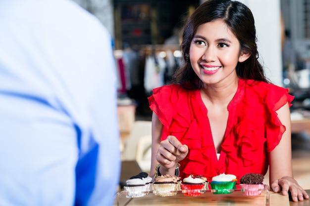Porträt von einrichtungskleinen kuchen einer netten asiatin in einem kühlen café