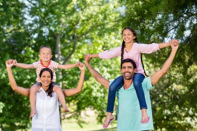 Porträt von eltern, die ihre kinder auf schulter im park tragen