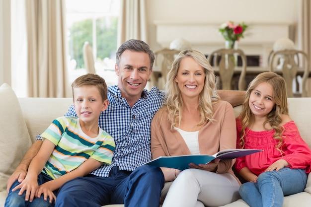 Porträt von eltern und kindern, die zusammen auf sofa mit fotoalbum sitzen