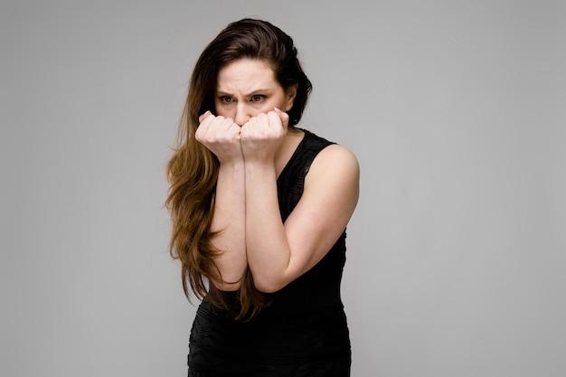 Porträt von emotionalem recht überzeugtem plus das größenmodell, das im studio steht, frustrierte sich auf grau