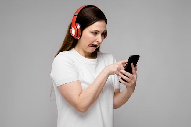 Porträt von emotionalem schönem glücklichem plus größenmodell in den kopfhörern, die im handy hört musik schauen