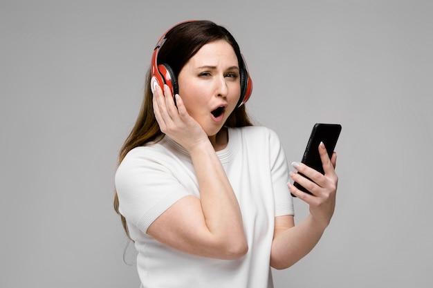 Porträt von emotionalem schönem glücklichem plus größenmodell in den kopfhörern, die in camera halten den handy hört musik schauen