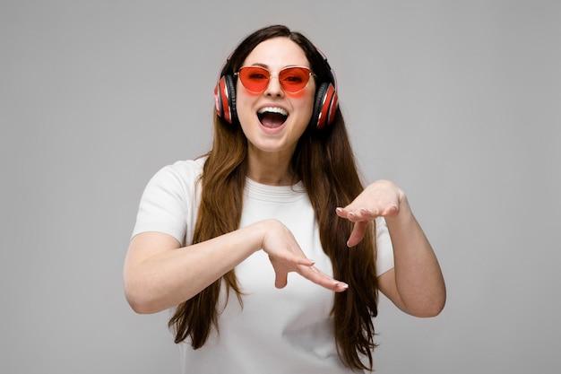 Porträt von emotionalem schönem glücklichem plus größenmodell in den kopfhörern und in sonnenbrille, die musik stehen und hören
