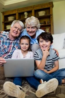 Porträt von enkelkindern und großeltern mit laptop im wohnzimmer