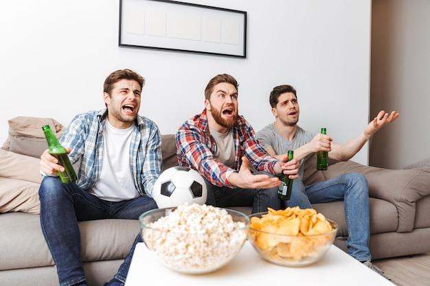 Porträt von enttäuschten jungen männern, die fußball schauen, während sie zu hause mit bier und snacks drinnen sitzen