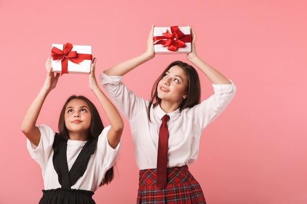 Porträt von erfreuten mädchen in der schuluniform, die geschenkboxen halten, während isoliert über roter wand stehen