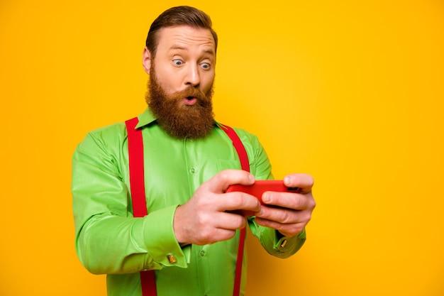 Porträt von erstaunten funky blogger mann verwenden smartphone lesen social media gefälschte nachrichten beeindruckt schreien wow omg tragen gut aussehen outfit isoliert glanzfarbe