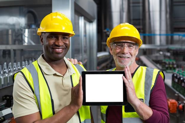 Porträt von fabrikarbeitern, die digitales tablett im werk halten