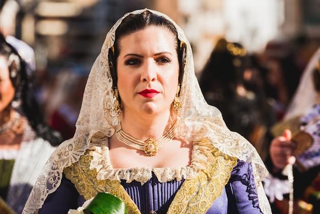 Porträt von falleras-frauen, die das traditionelle kostüm von fallas am tag des angebots an die jungfrau während der parade tragen