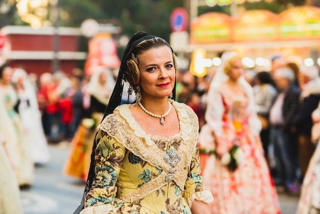 Porträt von falleras-frauen, die das traditionelle kostüm von fallas tragen, das der jungfrau während der parade durch die straßen von valencia anbietet